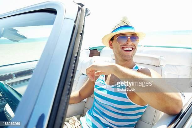 Junger Mann mit Sonnenbrille und Hut, während Sie dem Auto