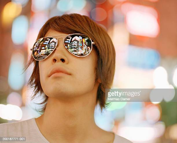Young man wearing sunglasses, close-up signage reflected in glasses