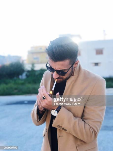 young man wearing sunglasses igniting cigarette while standing outdoors - 25 29歳 ストックフォトと画像