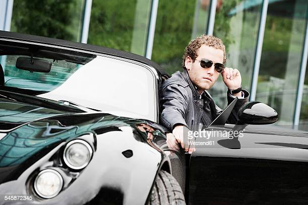 Young man wearing sunglasses sitting in black sports car