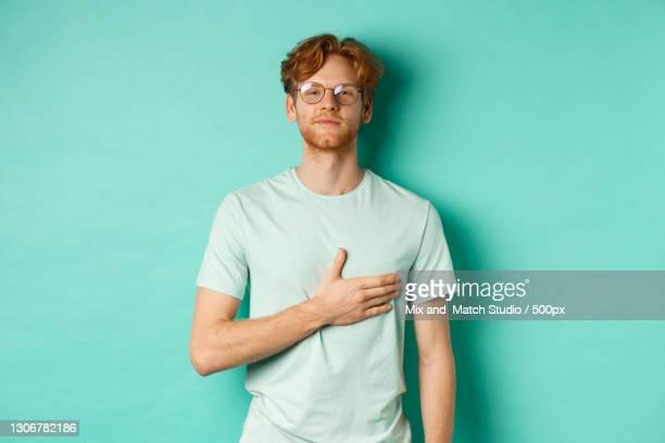 young man wearing sunglasses while standing against blue background - geschworener stock-fotos und bilder