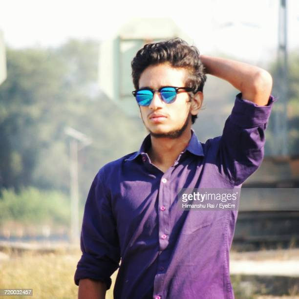 young man wearing sunglasses with hand in hair standing on field - vestido roxo - fotografias e filmes do acervo