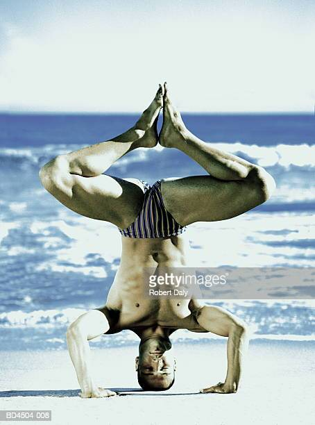Young man wearing swimming trucks, doing headstand on beach