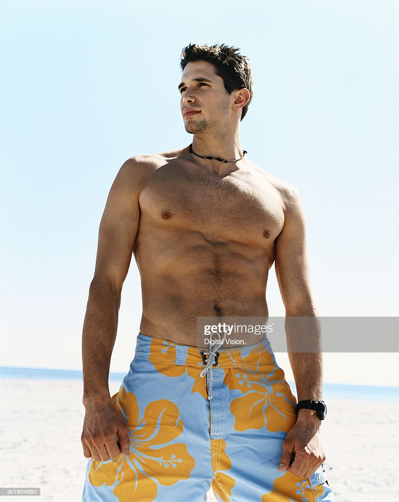 Young Man Wearing Swimming Trunks on a Beach and Looking Sideways : Stock Photo