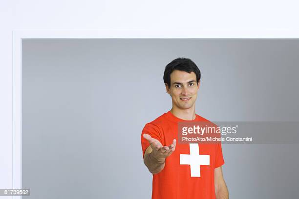 young man wearing tee-shirt with plus symbol, holding out hand, smiling at camera - cruz roja fotografías e imágenes de stock