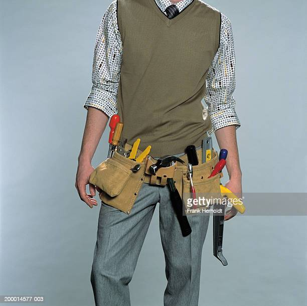 Young man wearing tool belt, mid section