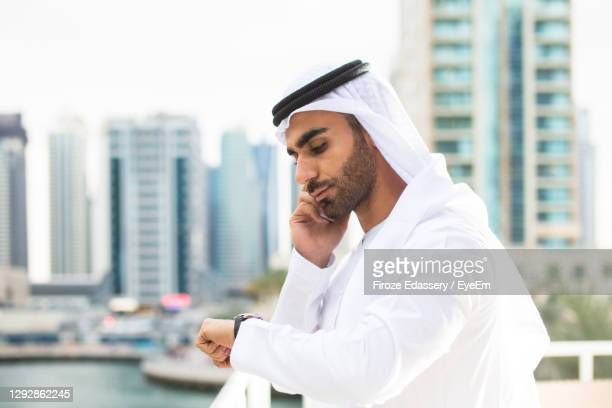 young man wearing traditional clothing talking over smart phone - middle east stock pictures, royalty-free photos & images