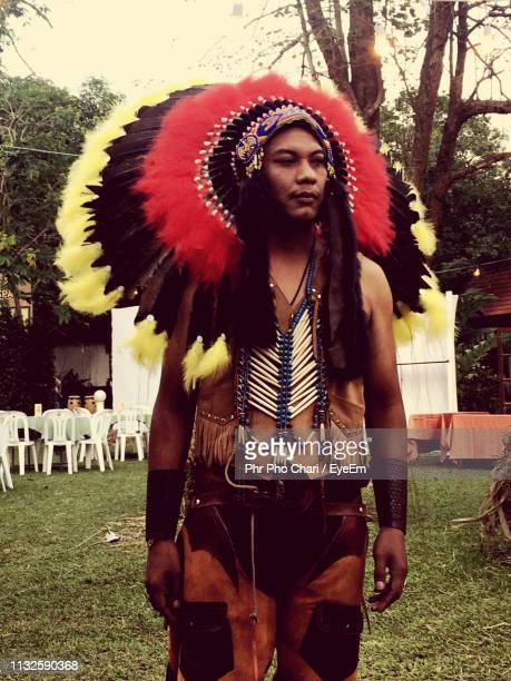 young man wearing traditional headdress on field - north american tribal culture stock pictures, royalty-free photos & images