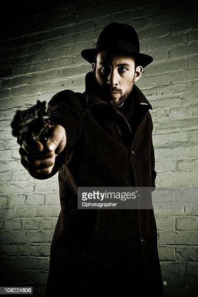 young man wearing trench coat and hat pointing gun - trench coat stock pictures, royalty-free photos & images