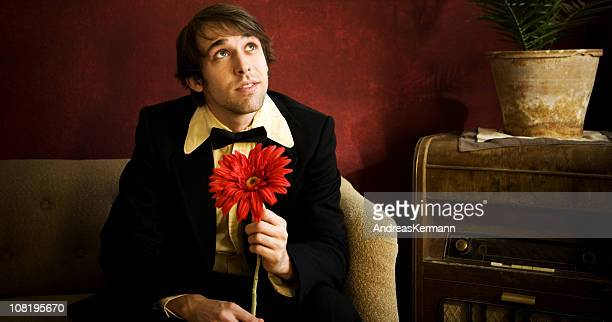 Young Man Wearing Tuxedo and Holding Large Flower