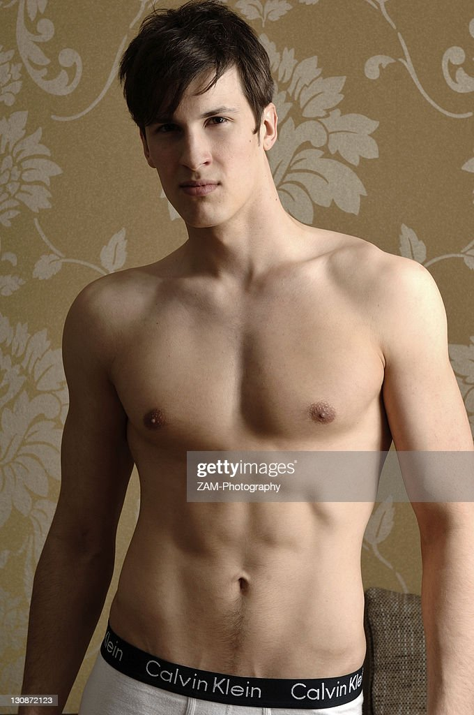 Young Man Wearing Underwear Standing In Front Of Nostalgic Wallpaper Stock Photo