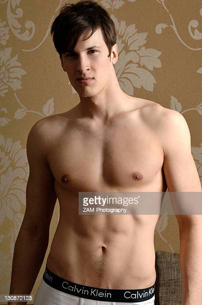 Young man wearing underwear standing in front of nostalgic wallpaper