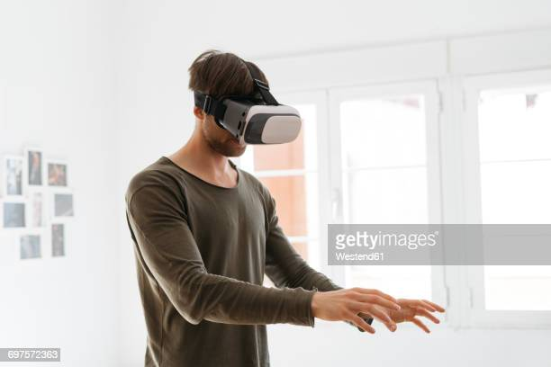 Young man wearing virtual reality glasses at home