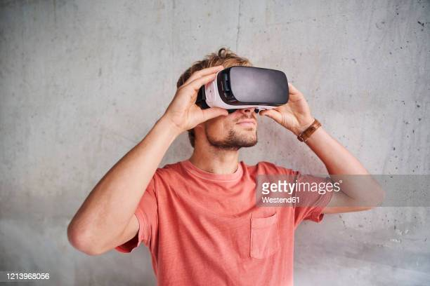 young man wearing virtual reality goggles - virtual reality simulator stock pictures, royalty-free photos & images