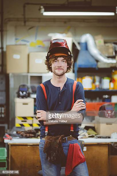 Young man wearing welding helmet in a workshop