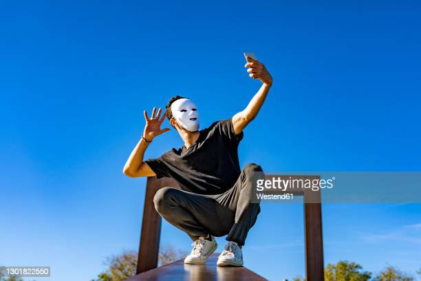 young man wearing white mask waving hand to video call through mobile phone while crouching on retaining wall - actor foto e immagini stock
