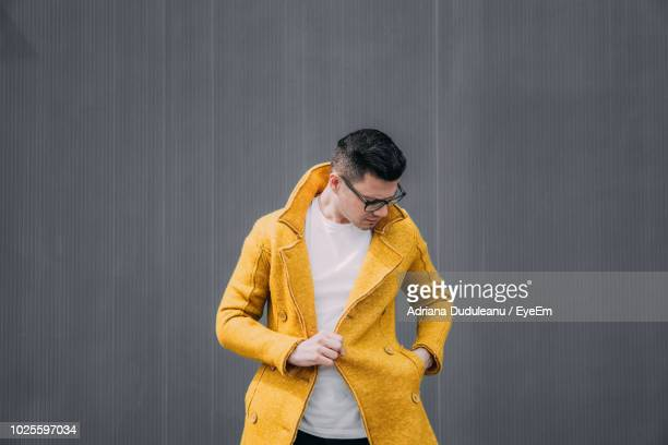 young man wearing yellow jacket against gray wall - jacket stock pictures, royalty-free photos & images