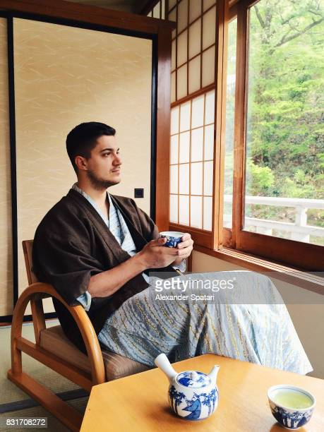 Young man wearing yukata drinking green tea in ryokan