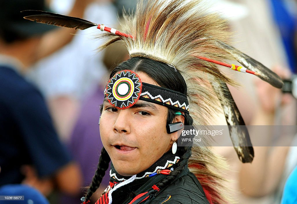 A young man wears his native Indian headress and modern-day mobile phone earpiece, during a concert at Forks Park, attended by Britain's Queen Elizabeth II and Prince Philip, Duke of Edinburgh, on July 3, 2010 in Winnipeg, Canada. The Queen and Duke of Edinburgh are on an eight day tour of Canada, starting in Halifax and finishing in Toronto, to celebrate the centenary of the Canadian Navy and to mark Canada Day on July 1st. On July 6th the royal couple will make their way to New York where the Queen will address the UN and visit Ground Zero.