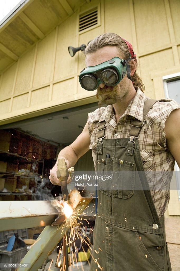 Young man welding metal : Stockfoto