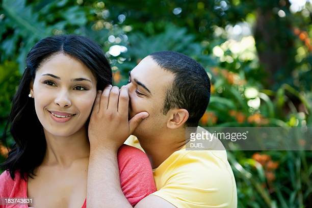Young man whispering in woman's ear