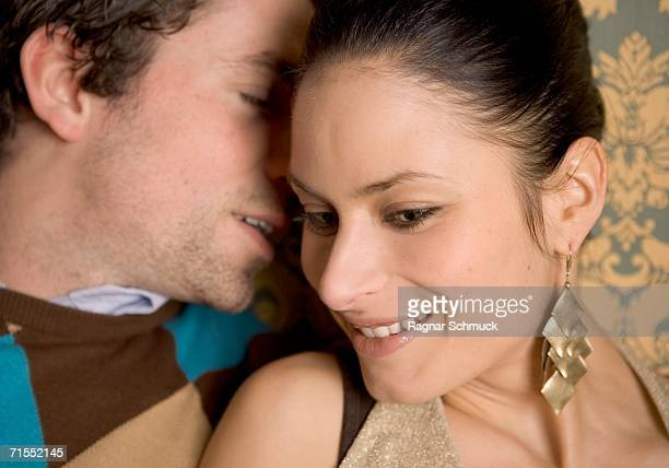 Young man whispering into young woman?s ear