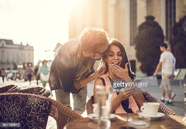 Junger Mann Flüstern schockierend Dinge zu seiner Freundin im Café.