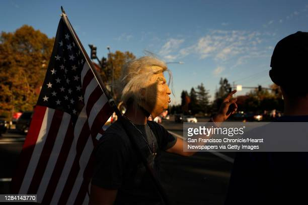 """Young man, who didn't want to be identified, wears a Donald Trump mask while doing supporters of US president Donald Trump taking part in a """"Trump..."""