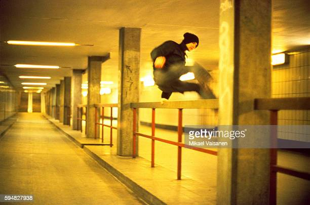 A young man who is jumping over a railing, subway