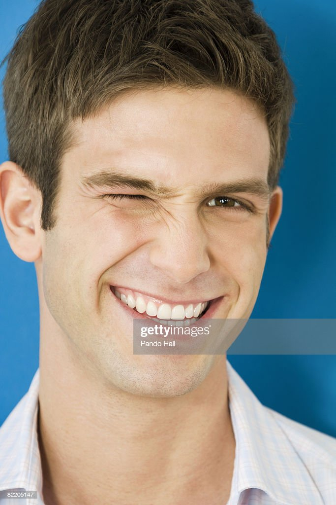 Young man winking, smiling, portrait : Stock Photo