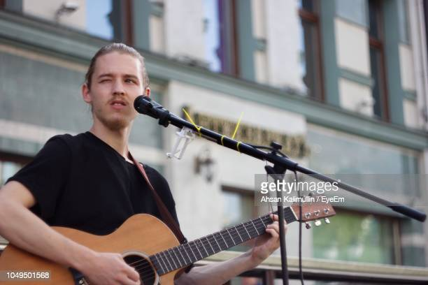 Young Man Winking While Playing Guitar In City
