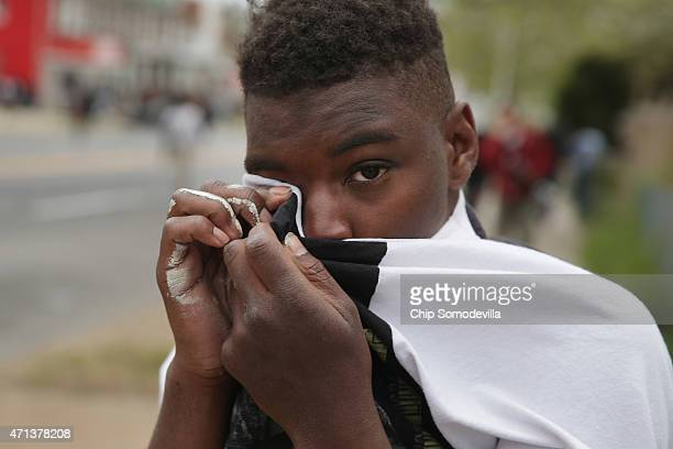 A young man wipes his face after being hit with pepper spray during violent protests near the Mondawmin Mall following the funeral of Freddie Gray...