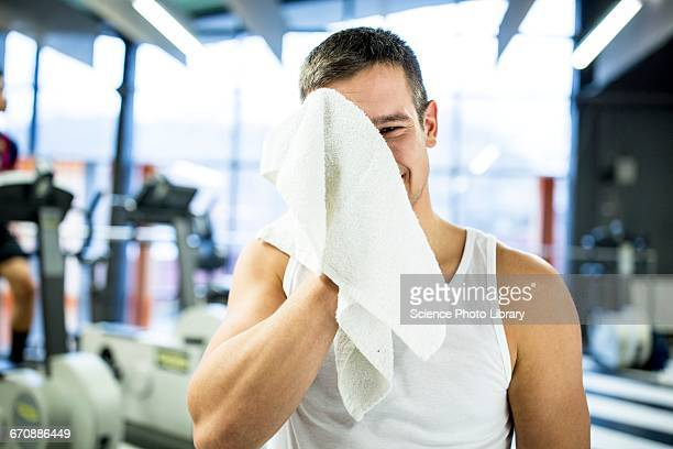 Young man wiping his sweat with towel