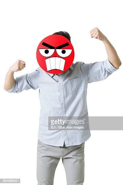 Young man with a angry emoticon face in front of his face