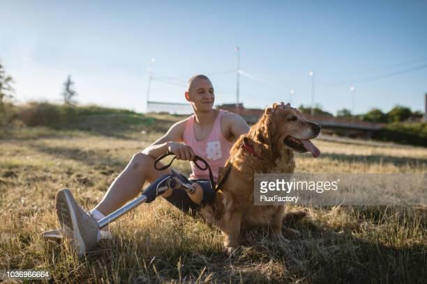 young man with a artificial leg petting his dog - pessoas com deficiência imagens e fotografias de stock