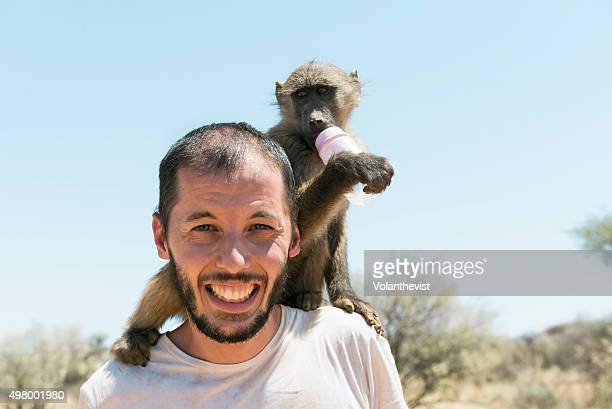 young man with a baby baboon on his shoulders in namibia, southern africa - chacma baboon stock photos and pictures