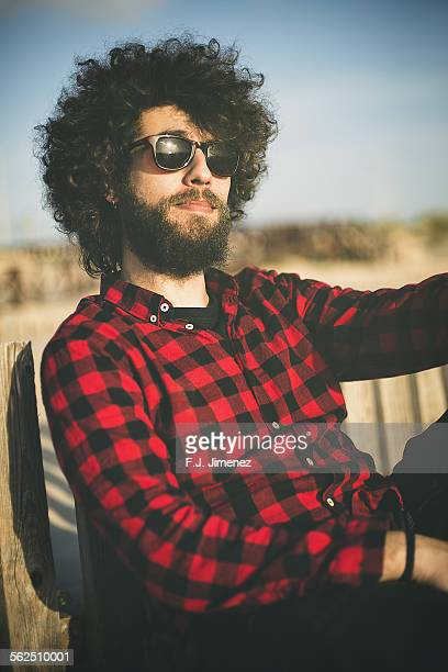 Young man with a beard, afro hair and plaid shirt