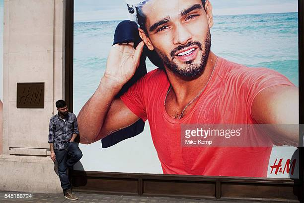 Young man with a beard standing outside a large scale advertising poster for fashion retail outlet HM in London United Kingdom The man having a...