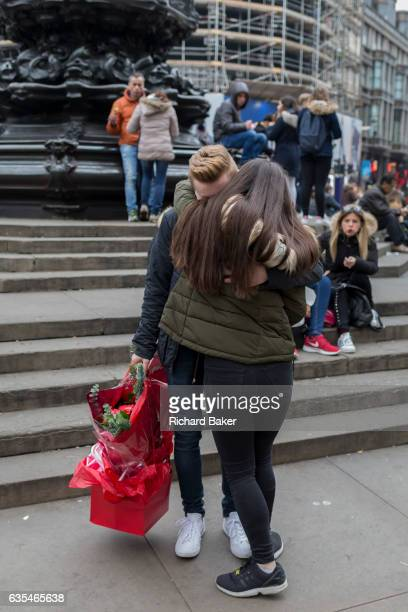 A young man with a bouquet of red roses gets a hug from his girlfriend on 15th February 2017 in Piccadilly Circus London borough of Westminster...