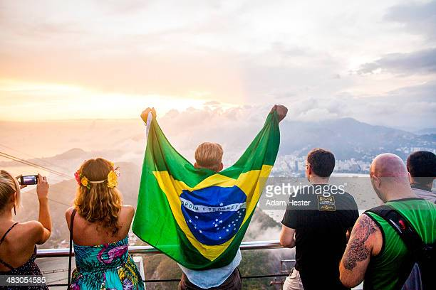 A young man with a brazilian flag around his back.