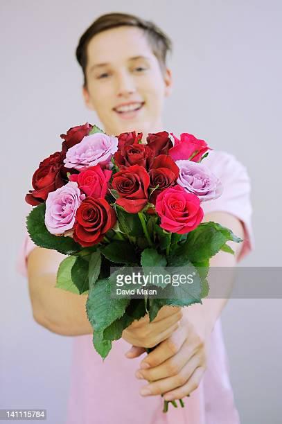 young man with a bunch of roses. - david ramos fotografías e imágenes de stock