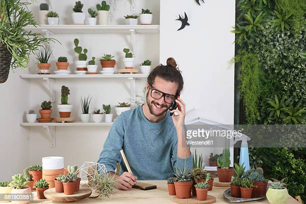 Young man with a collection of cacti on the phone