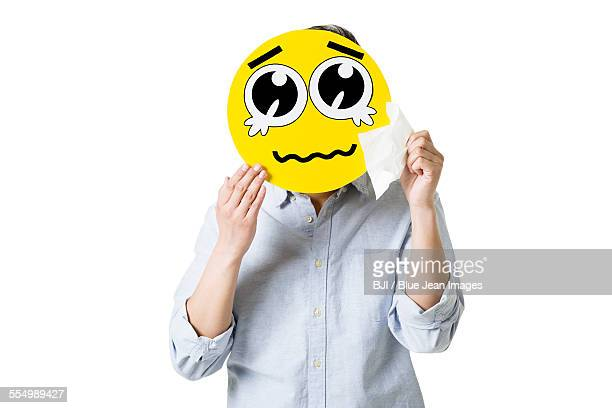 Young man with a crying emoticon face in front of his face