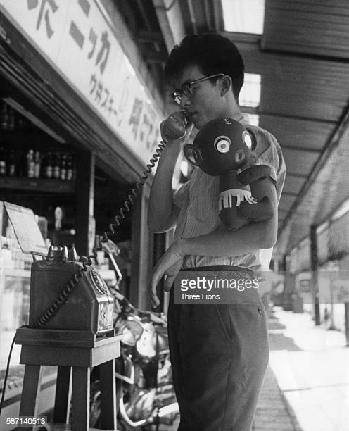 A young man with a DakkoChan doll made by the Takara toy company Japan circa 1960 The doll was later criticised for being a racist caricature