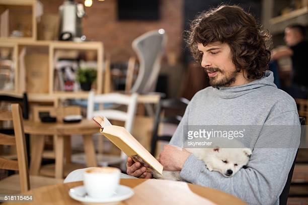 若い男性、犬は、読書でのカフェ。