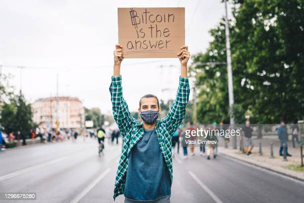 young man with a face mask and a poster in his hands about bitcoin. young activist / protester. blockchain activist - extremism stock pictures, royalty-free photos & images