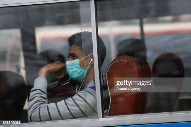 A young man with a face mask sits in a bus in Kathmandu Nepal on March 28 2017 Construction and road expansion works increase in number of vehicles...