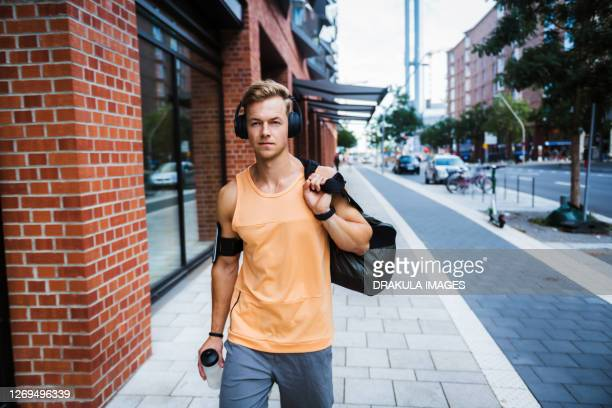 young man with a gym bag in a city - スポーツバッグ ストックフォトと画像
