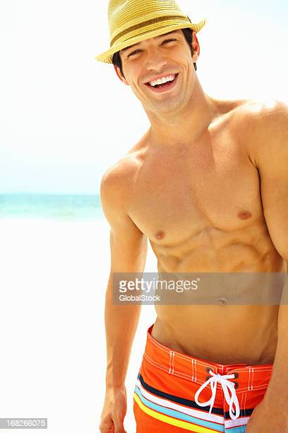 Young man with a hat on the beach