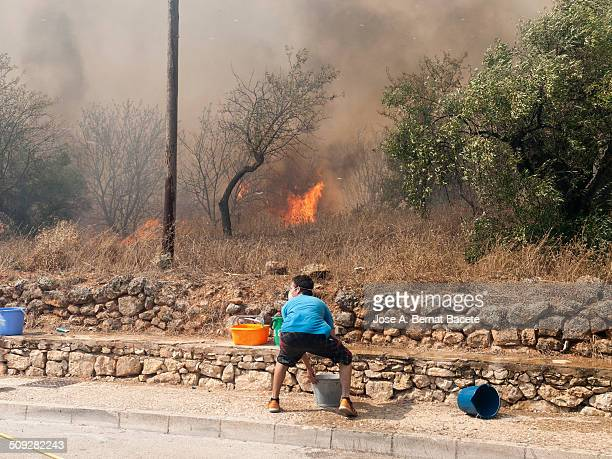 Young man with a mask and in times of great nervousness putting out the flames of a forest fire with buckets of water, the fire is on the verge of a...